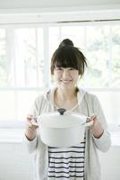 笑顔で鍋を持つ10代女子大生