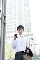 営業中、スマートフォンを使うビジネスマン