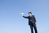 紙飛行機を持つ20代ビジネスマン
