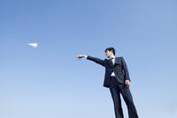 紙飛行機を飛ばす20代ビジネスマン