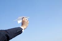 紙飛行機を持つ20代ビジネスマンの手