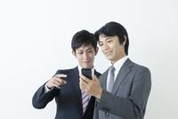 スマートフォンを見ながら話すビジネスマン
