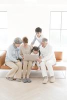 ソファに座りノートパソコンを見る三世代家族 10161012584  写真素材・ストックフォト・画像・イラスト素材 アマナイメージズ
