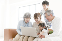 ソファに座りノートパソコンを見る三世代家族