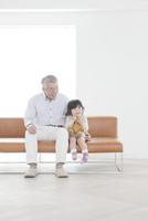 ソファに座るおじいちゃんと孫娘