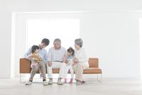 ソファに座る祖父,祖母,息子,孫娘2人