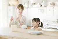 キッチンでくつろぐ母親と娘