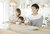 キッチンでくつろぐ夫婦と娘