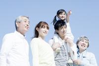 青空の下に立つ三世代家族