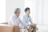 ソファに座って話す笑顔の父親と息子