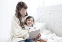 ベッドで一緒に本を読む母親と娘