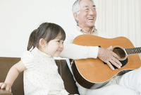 ギターを弾いて遊ぶ祖父と孫娘 10161012931  写真素材・ストックフォト・画像・イラスト素材 アマナイメージズ