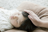 祖母の手とお昼寝中の女の子