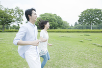 公園で手をつないで走るカップル