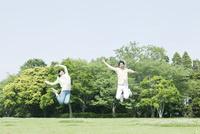芝生でジャンプする女性と男性