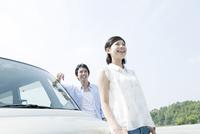 車の前に立つ女性と男性
