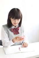 机で携帯電話を見る高校生
