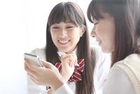 携帯電話を一緒に見る高校生2人