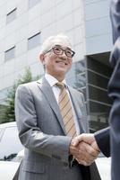車の前で握手をする中高年ビジネスマン