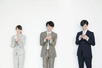 携帯電話を使うスーツ姿の男性と女性