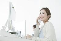 オフィスで電話を使うヤングビジネスウーマン