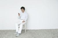 椅子に座ってスマホを見る60代の男性 10161014545  写真素材・ストックフォト・画像・イラスト素材 アマナイメージズ