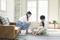 部屋でくつろぐ若い夫婦と子供