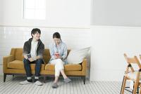 ソファーに座る20代カップル