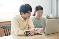 パソコンを使う20代カップル