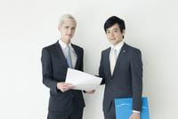 資料を見るスーツ姿の20代の外国人男性と日本人男性