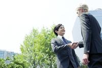 握手をするスーツ姿の20代の外国人男性と日本人男性