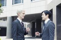 会話をするスーツ姿の20代の外国人男性と日本人男性