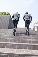 階段を駆け上がるスーツ姿の20代の外国人男性と日本人男性
