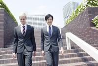 階段を降りるスーツ姿の20代の外国人男性と日本人男性