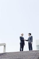 階段の上で会話をするスーツ姿の20代の外国人男性と日本人男性
