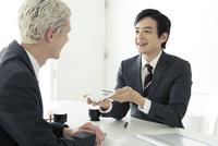 電卓を使うスーツ姿の20代の外国人男性と日本人男性