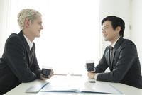 コーヒーを飲むスーツ姿の20代の外国人男性と日本人男性