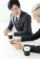 スマホを見るスーツ姿の20代の外国人男性と日本人男性