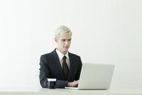 パソコンを使うスーツ姿の20代の外国人男性