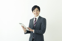 タブレットを使うスーツ姿の20代の日本人男性