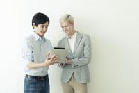 タブレットを使う20代の外国人男性と日本人男性