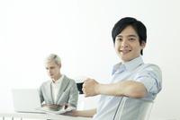 休憩する20代の日本人男性とパソコンを使う外国人男性