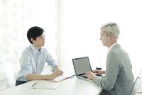 会話をする20代の日本人男性と外国人男性