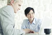 パソコンを見る20代の日本人男性と外国人男性