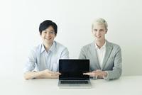 パソコンを指差す20代の日本人男性と外国人男性