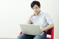 椅子に座りパソコンを使う20代の日本人男性