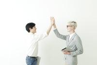 ハイタッチする20代の日本人男性と外国人男性