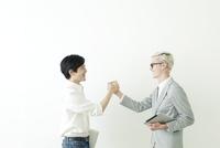 握手する20代の日本人男性と外国人男性