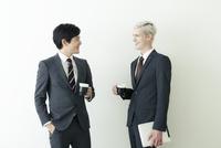 談笑するスーツ姿の20代の外国人男性と日本人男性