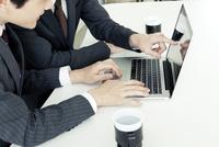 パソコンを使うスーツ姿の20代の男性の手元